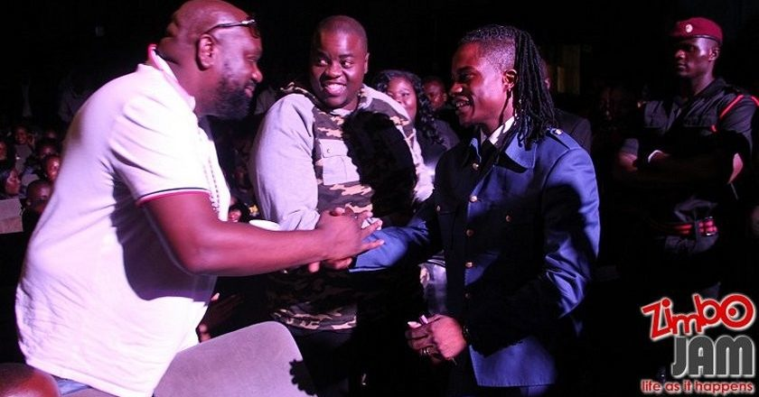 Andy Muridzo thanking Tazvi Mhaka for buying his CD for $900 whilst Sir Wicknel looks on after buying a copy for $1000